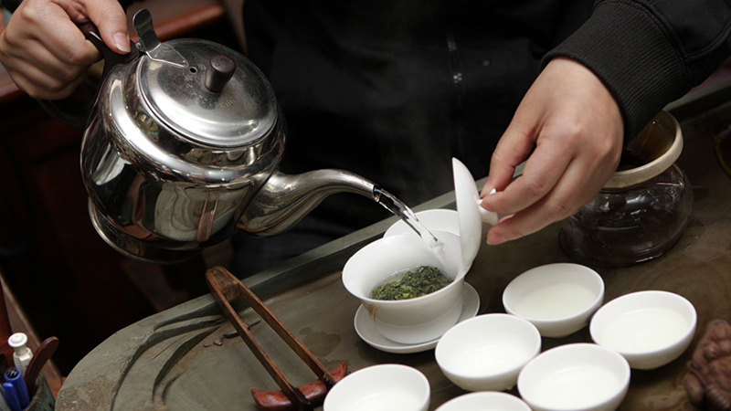 Man pouring hot water in tea leaves in white tea cups in Beijing