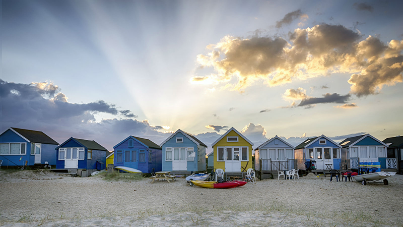 Colorful beach houses perched on white sand in Bournemouth